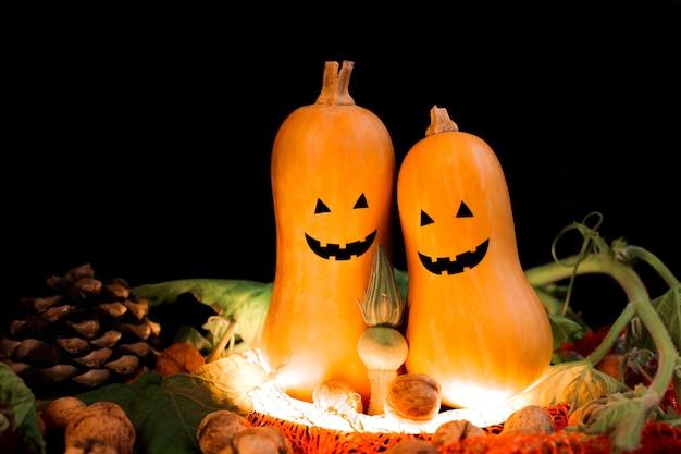 Две тыквы с лицами на хэллоуин на черном фоне при свете фонаря в окружении орехов, шишек и листьев. фото высокого качества