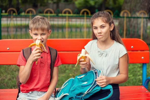 Два друга ученика, девочка и мальчик, сидят на скамейке возле школы и едят бананы