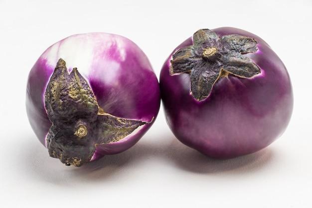 2つの紫色のナスがクローズアップします。白色の背景。