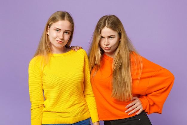 두 개의 의아해 잠겨있는 젊은 금발 쌍둥이 자매 소녀 서, 파스텔 바이올렛 파란색 벽에 고립 된 생생한 화려한 옷을 입고. 사람들이 가족 라이프 스타일 개념.
