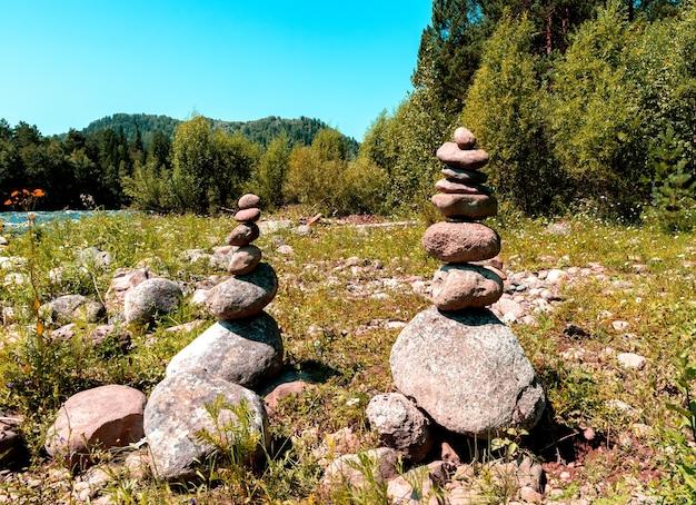 山の川のほとりに石で作られた2つのピラミッド。権力のアルタイ場所