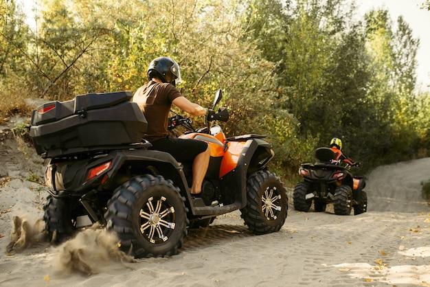 2人のクワッドバイクライダーが森の中を旅します、正面図