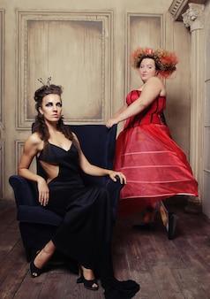 カーニバルドレスを着た2人の女王。黒と赤。休日の写真。