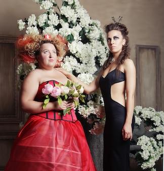 Две королевы в карнавальных нарядах. черный и красный. праздничная картинка.