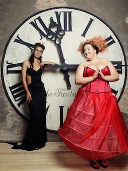 時計の横でポーズをとる2人の女王。休日の写真。