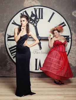 Две королевы позируют рядом с часами. праздничная картинка.