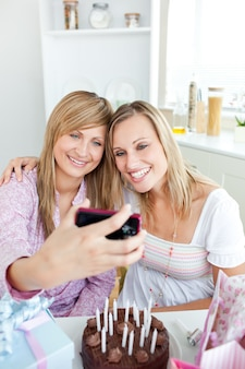 Two radiant female friends taking pictures during a birthday party in the kitchen