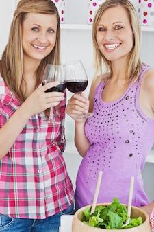 부엌에서 요리 한 후 와인을 마시는 두 명의 빛나는 여성