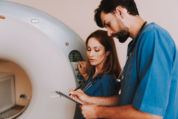 Two radiologists setting mri machine carefully.