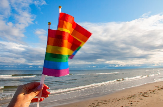 Two rainbow flags in the hands of a woman against a background of blue sky and sea