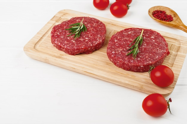 Two raw beef burger patties on wooden board