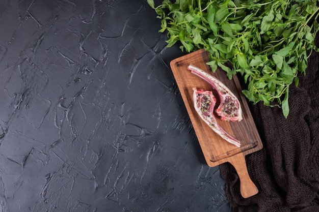 Two raw beef chops on wooden board with fresh mint.