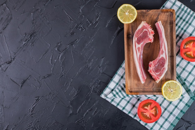 Two raw beef chops on wooden board with lemon and tomato slices.