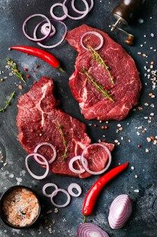 다크 슬레이트 또는 콘크리트 배경에 향신료, 양파, 칠리를 곁들인 생 쇠고기 스테이크 2개. 평면도