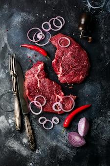 향신료, 양파, 칠리 다크 슬레이트 또는 콘크리트 배경에 두 개의 원시 쇠고기 스테이크. 평면도