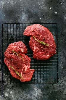 Two raw beef steak with spices, onions and chili on dark slate or concrete table. top view