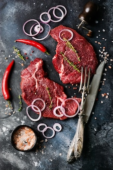 Two raw beef steak with spices, onions and chili on dark slate or concrete.
