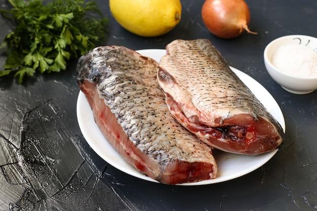 塩、レモン、タマネギ、ディル、パセリ:暗い背景と材料に対してプレート上の2つの生の鯉。