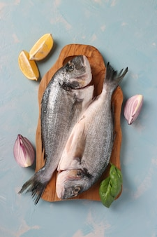 Two raw fish dorado with basil and lemon on wooden board on light blue table, vertical format. top view