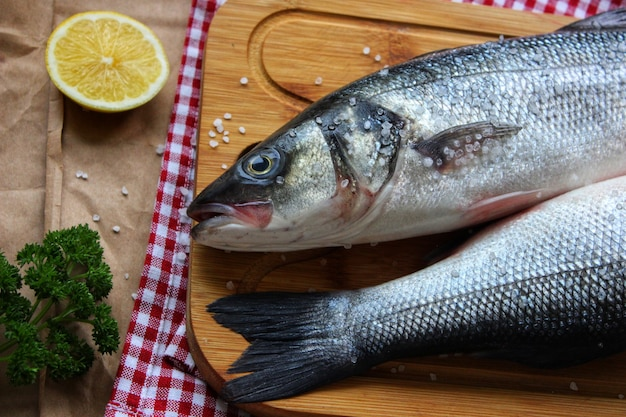 レモンスライスのクローズアップテクスチャまたは背景で飾られたまな板上の2つの生の魚