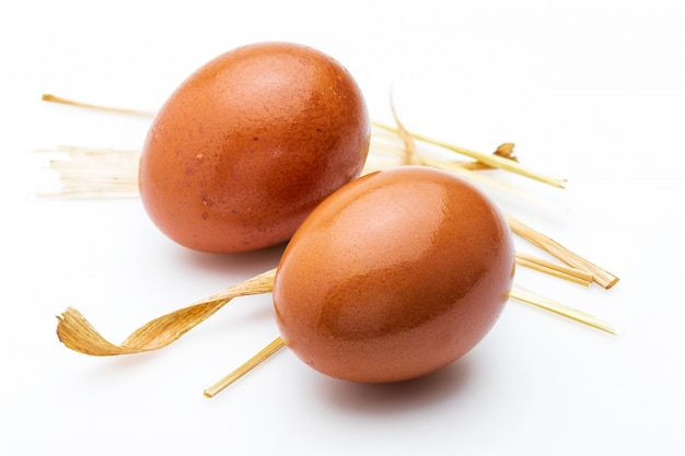Two raw and fresh eggs with straw. isolated