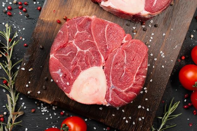 어두운 배경, 체리 토마토와 향신료에 두 개의 원시 신선한 차 돌 박이 고기 스테이크. 확대.