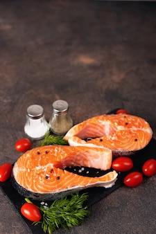 Two raw fresh salmon on a dark background