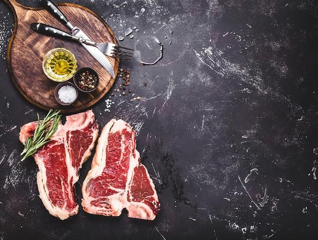 두 개의 원시 대리석 고기 스테이크 t-bone, 조미료, 허브, 돌 배경.