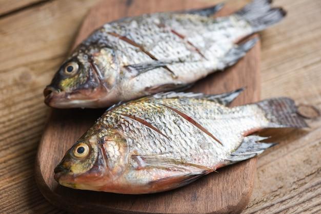 Две сырой нильской пресноводной рыбы тилапии на деревянной доске / свежая рыба тилапия для приготовления пищи
