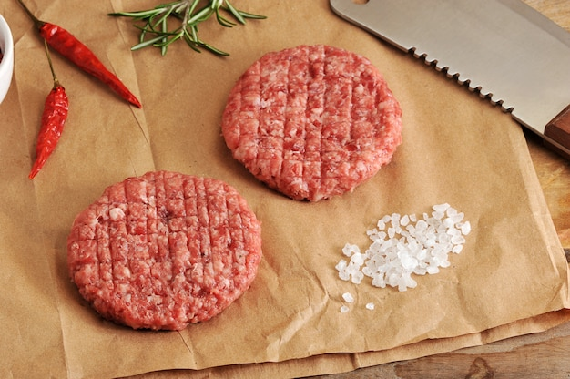 Two raw patties of minced meat in the form of a circle and a knife machete to paper