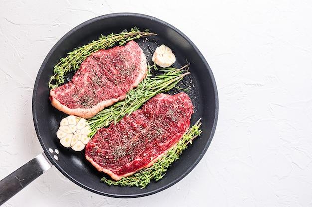 두 개의 생 피칸하 유기농 쇠고기 스테이크가 허브와 마늘을 곁들인 팬에 그릴 준비가 되어 있습니다. 흰색 질감된 배경 위에 텍스트를 위한 공간이 있는 위쪽 보기.