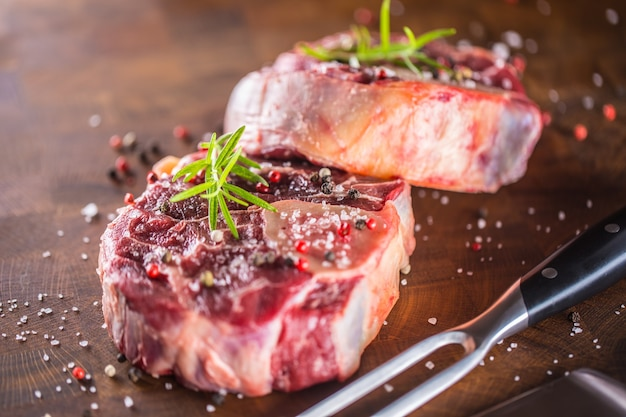 포크와 나이프로 나무 정육점 보드에 두 개의 원시 조각 쇠고기 정강이.