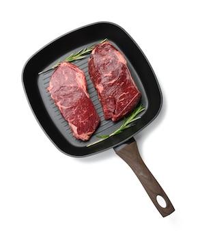 Два сырых куска говядины в черной квадратной сковороде для гриля, стейки, изолированные на белой поверхности, вид сверху