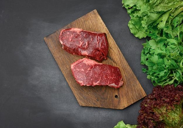 Два сырых куска говяжьего стейка на коричневой деревянной доске, черный стол, рядом с зелеными листьями салата, вид сверху