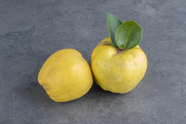 Due frutti di mela cotogna crudi isolati su una superficie grigia