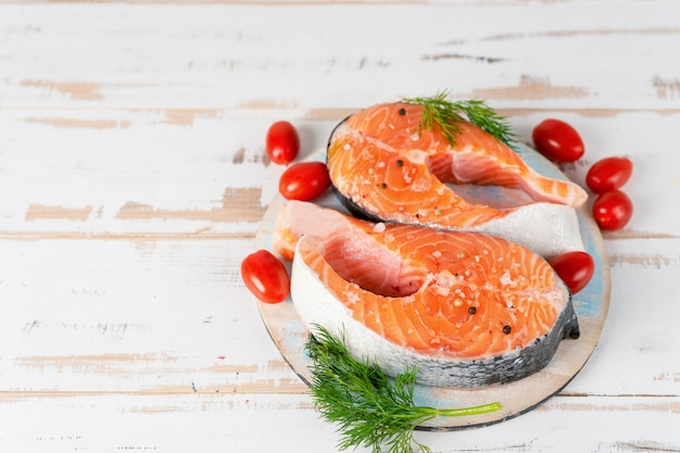 Two raw salmon steaks with tomatos on the wooden table