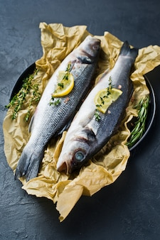 Two raw sea bass on kraft paper with rosemary, thyme and lemon.