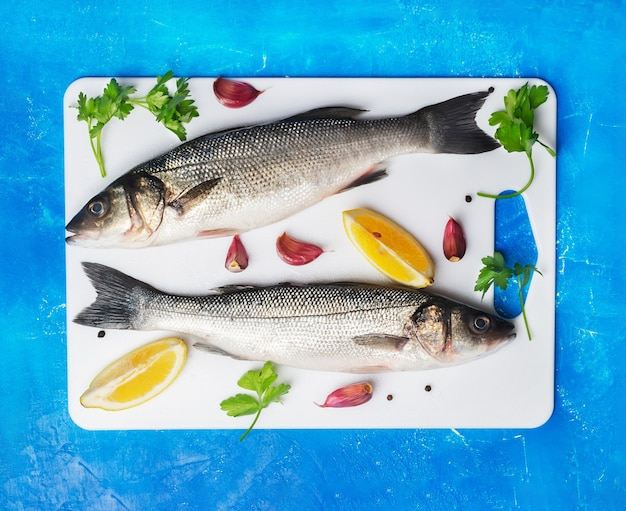 Two raw seabass with spices and lemon on white cutting board