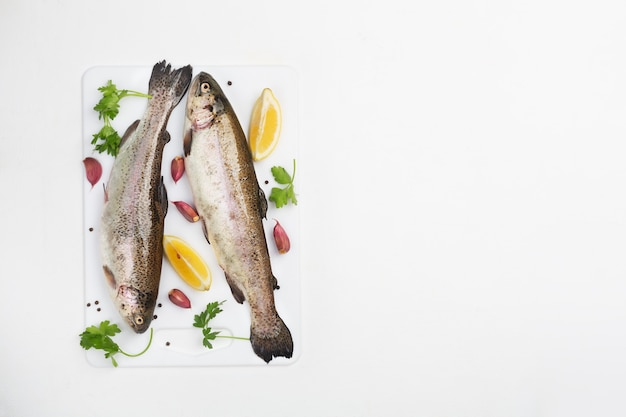 Two raw trouts with spices and lemon on a white space, top view