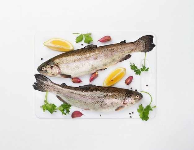 Two raw trouts with spices and lemon on a white space