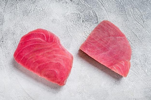Два сырых стейка тунца на деревенском столе. белый фон. вид сверху.