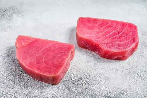 Два сырых стейка тунца на деревенском столе.