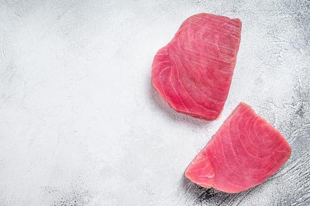 Два сырых стейка тунца на деревенском столе