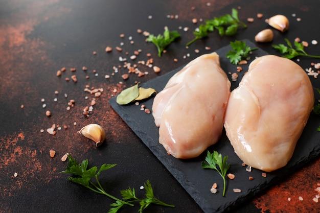 검은 접시에 생 쌀된 신선한 닭고기 필 레 두 개. 신선한 가금류 고기. 평면도. 공간 복사
