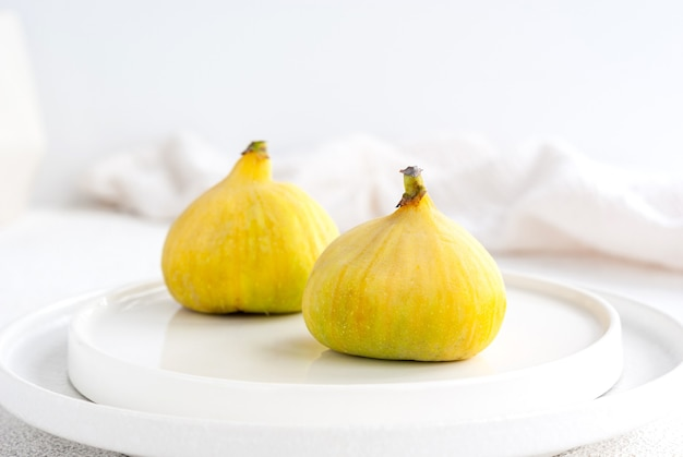Two raw yellow tiger figs on a white plate ready to eat