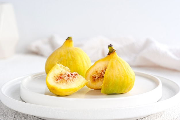 Two raw yellow tiger figs on a white plate with one piece cut off