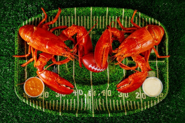 Два готовых к употреблению омаров с шариком и соусом на зеленой тарелке. футбольный ужин.