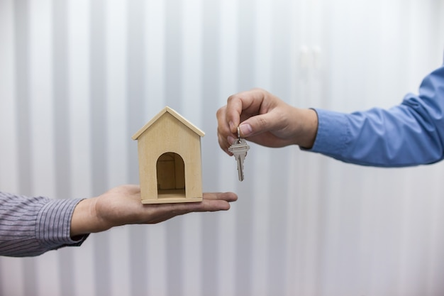 Two real estate brokers hold keys and house models