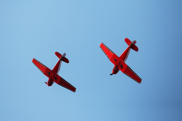 Two red airplanes in blue sky