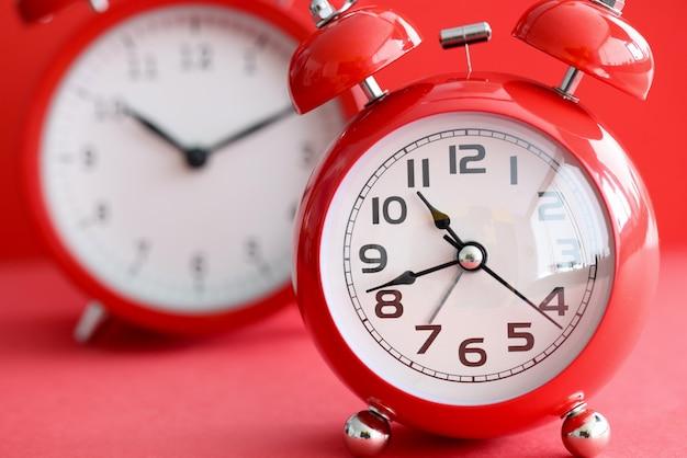 시간이 다른 두 개의 빨간색 알람 시계. 모든 것을 유지하고 시간을 올바르게 관리하는 방법 개념